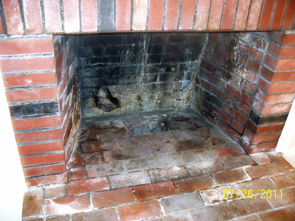 Problems with water saturation in the chimney resulted in staining in the  firebox. The walls are also damaged above the mantel.